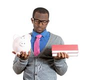 Man holding books and piggy bank Royalty Free Stock Image