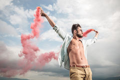 Man holding in both hands smoke producing tubes Royalty Free Stock Photo
