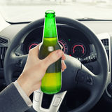 Man holding bottle of beer while driving - 1 to 1 ratio Stock Image