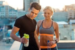 Man holding bottle of cocktail. Man holding bottle of protein cocktail to gain muscles. Couple of runners on background of an urban city, having a rest after stock images