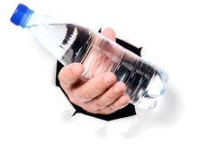 Man is holding bottle through a hole Royalty Free Stock Photography