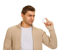 Man holding a bottle of medicine. Young man holding a bottle of medicine Royalty Free Stock Photography