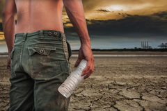 Man holding a bottle of water land to the ground dry cracked. Stock Images