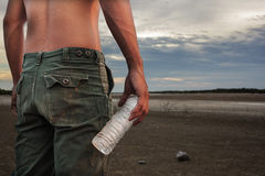 Man holding a bottle of water land to the ground dry cracked. Stock Image