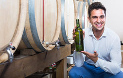 Man holding bottle of wine in cellar with woods Royalty Free Stock Image
