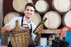 Man  holding bottle of wine and standing in alcohol section Royalty Free Stock Photo