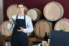 Man  holding bottle of wine and standing in alcohol section Royalty Free Stock Photography