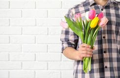 Man holding bouquet of beautiful spring tulips near brick wall, closeup with space for text. International Women`s Day stock photography