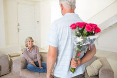 Man holding bouquet behind back with woman sitting on couch Royalty Free Stock Photo