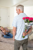 Man holding bouquet behind back with woman sitting on couch Stock Photo