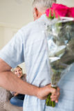 Man holding bouquet behind his back with woman sitting on couch Royalty Free Stock Photography