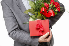 Man holding bouquet of carnation flowers and red box with big bo Royalty Free Stock Images