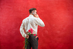 Man holding bouquet of carnations behind back Royalty Free Stock Photography