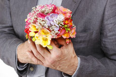 Man holding bouquet of colorful freesia flowers Stock Photos