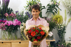 Man holding bouquet of flowers beside display in flower shop, smiling, front view, portrait Royalty Free Stock Photos