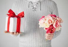 Man holding bouquet of flowers and gift box Royalty Free Stock Image