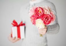 Man holding bouquet of flowers and gift box Stock Photos