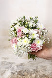 Man holding bouquet of pink roses, white chrysanthemums and gyps Royalty Free Stock Photo