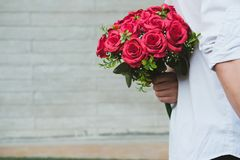 Man holding bouquet of red roses behind his back. boyfriend surp Royalty Free Stock Photo