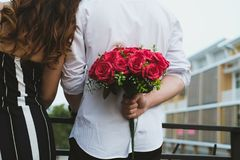 Man holding bouquet of red roses behind his back. boyfriend surp Royalty Free Stock Images