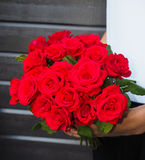 Man holding bouquet of red roses. A bouquet of red roses held by a man Stock Images
