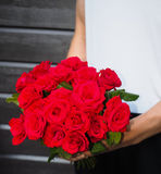 Man holding bouquet of red roses. A bouquet of red roses held by a man stock image