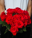 Man holding bouquet of red roses. A bouquet of red roses held by a man stock photography