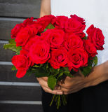 Man holding bouquet of red roses. A bouquet of red roses held by a man stock photos
