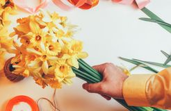 Man holding in bouquet of yellow daffodils flowers and colored ribbons with rope on white background. Top view Stock Photography
