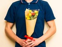 Man holding bouquet of yellow and orange roses. Women' s day, Va Stock Photos