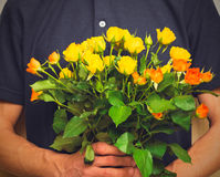 Man holding bouquet of yellow and orange roses. Women' s day, Va Stock Images