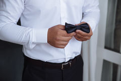 Man holding bow tie. Elegant gentleman clother. Stock Photo
