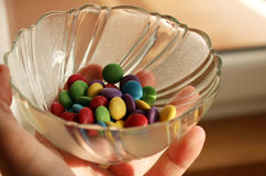 Man is holding bowl with chocolate candies Royalty Free Stock Photo