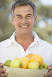 A man holding a bowl of fruit Royalty Free Stock Photography