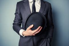 Man holding a bowler hat. Young man in suit is holding a bowler hat royalty free stock image