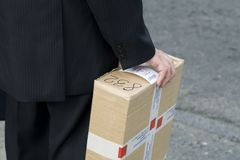 Man Holding Box. Man wearing a suit holding a brown cardboard box Royalty Free Stock Photo