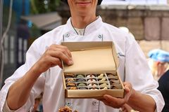 Man is holding a box of beautiful handmade candy. royalty free stock photography