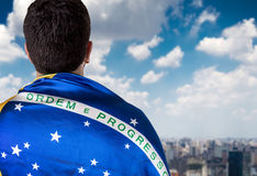 Man holding the Brazilian flag looking to the city Stock Photo