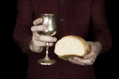 Man holding bread and wine for communion. Man in red holding bread and wine for Holy communion on a black background stock photo