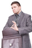Man holding a briefcase and making ok sign Stock Photos