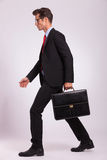 Man holding briefcase & walking Stock Image