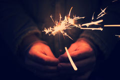 Man holding bright festive Christmas sparkler in hand, tinted ph Royalty Free Stock Photography