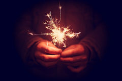 Man holding bright festive Christmas sparkler in hand, tinted ph Royalty Free Stock Image