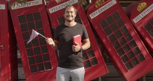 The man holding British flag and book, education abroad, learning language. The man holding British flag and book, education abroad, learning language stock video footage