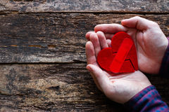 Man holding a broken heart glued. On a wooden background Stock Photography