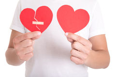 Man holding broken heart with plaster and normal paper heart Royalty Free Stock Photo