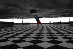 Man Holding a Broken Umbrella with Storm Brewing royalty free stock photo