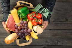 Man holding brown paper bag full of different healthy food. On a wooden table, top view Royalty Free Stock Image