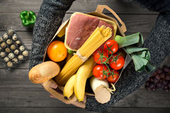 Man holding brown paper bag full of food. On wooden table, top view Stock Photography