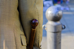 Man holding a brown walking stick Stock Images